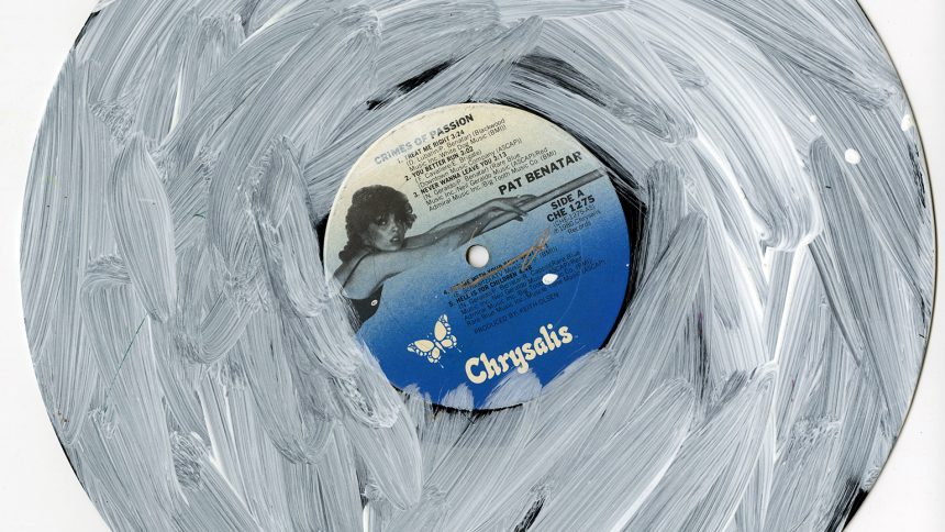 A vinyl record by Pat Benatar, Crimes of Passion, is overlaid with white acrylic paint by NIAD Studio Artist Christian Vassell.
