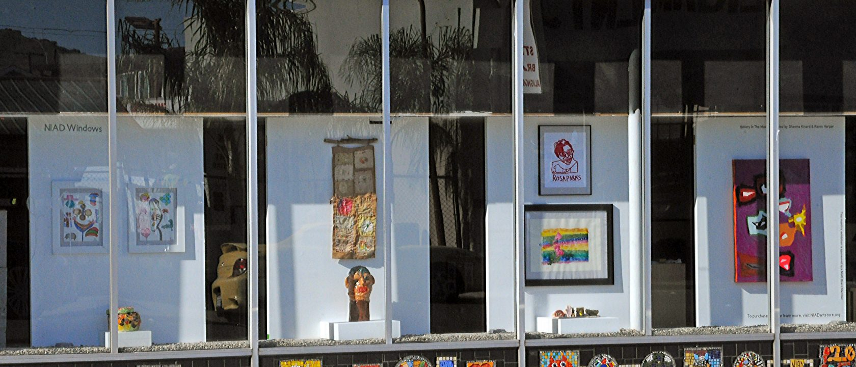 NIAD Art Centers front windows display a series of artworks by African American artists including ceramics, prints, and drawings.