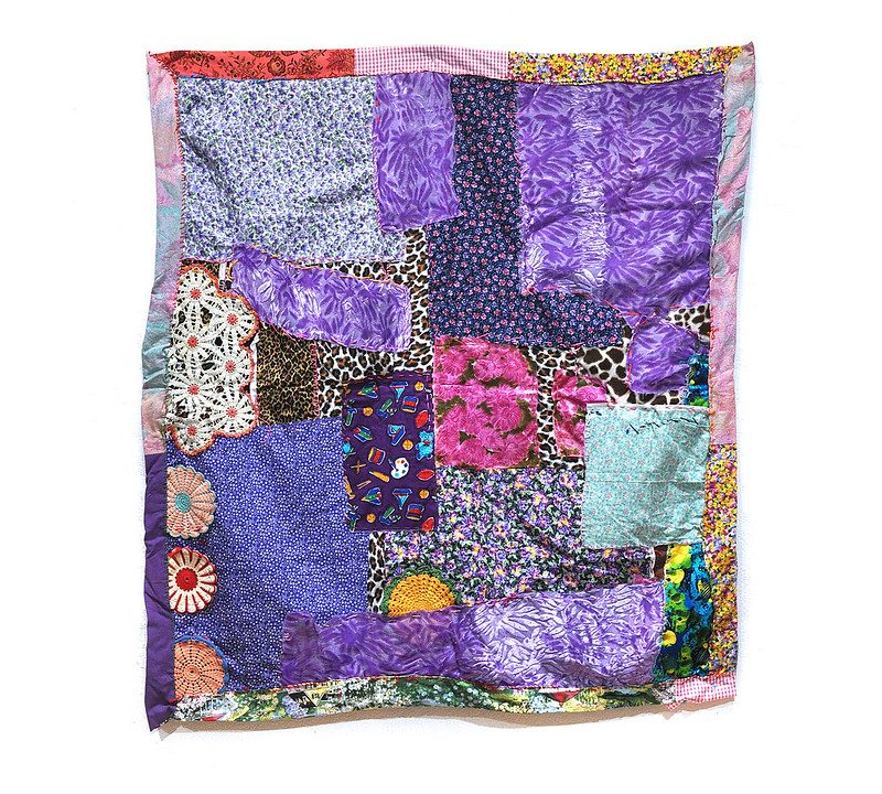 A collage of textiles of varying square and rectangle sizes, patterns and colors, layered on top of one another with some round, multi-colored doilie haped patches and a patchwork border.