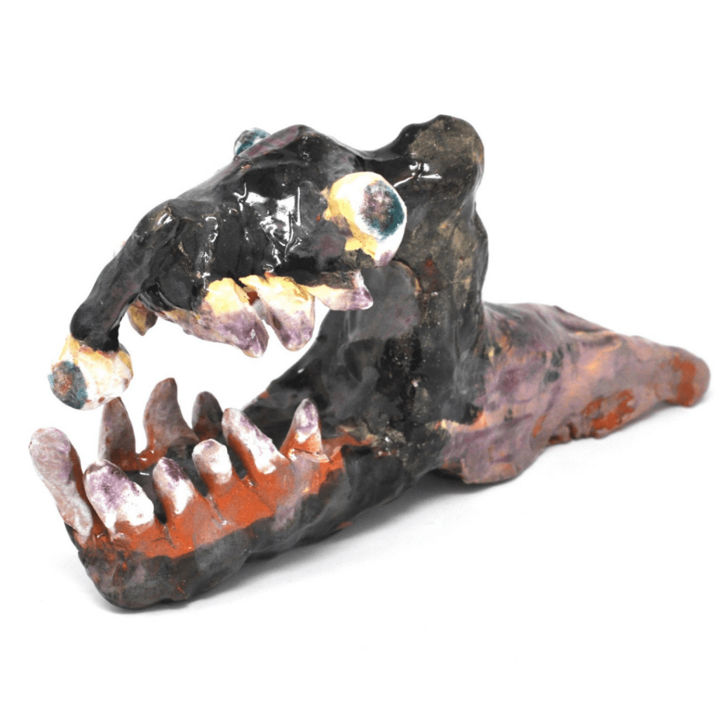 A ceramic piece with a slimy glaze of a gruesome figure with a reptilian head, a slug-like body, a lidless eye, and a jaw full of jagged teeth. One tooth has an eyeball growing from it.